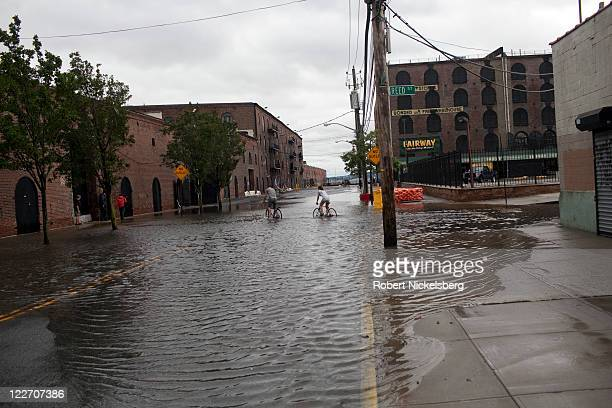 Local residents of Red Hook bicycle through flooded streets near the Fairway Supermarket August 28 2011 in the Brooklyn borough of New York City...