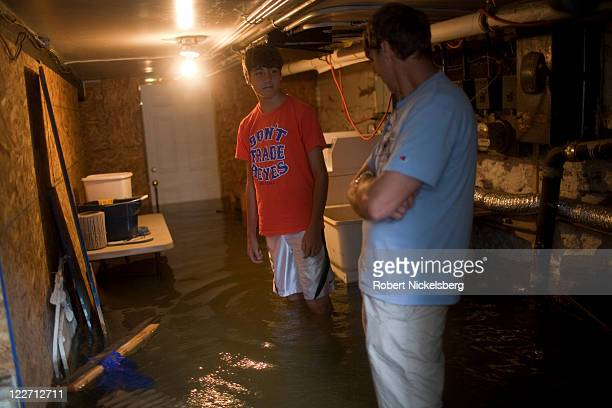 Local residents of Red Hook Philip Hogue and his son Avery Hogue check their basement for flood damage August 28 2011 in the Brooklyn borough of New...