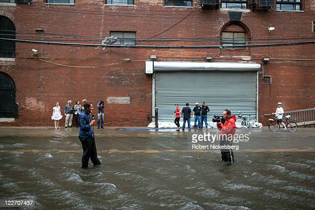 Local residents of Red Hook watch French journalists from the France 24 television station record a report August 28 2011 in the Brooklyn borough of...