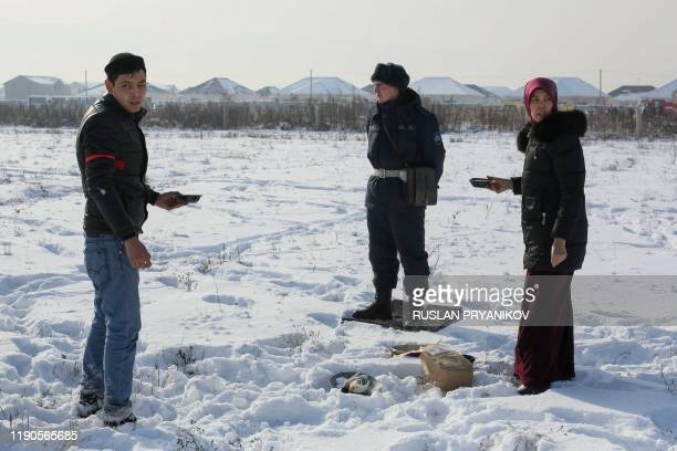 Local residents offer food to a soldier cordoning off the site of a passenger plane crash outside Almaty on December 27, 2019. - Some 12 people died...