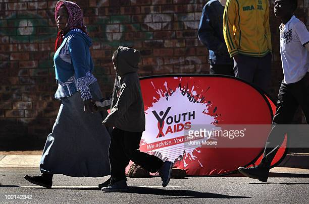 Local residents pass by an HIV awareness event held by the nonprofit Population Services International ahead of a World Cup game on June 16 2010 in...