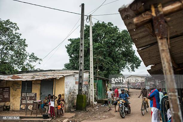 Local residents pass shacks and small businesses in Conakry Guinea on Saturday Sept 5 2015 While Guinea produces bauxite which is refined into...