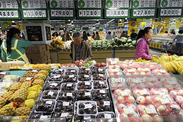 Local residents pick fresh fruits at a supermarket in Beijing on October 14 2011 China's consumer price index rose 61 percent in September from a...