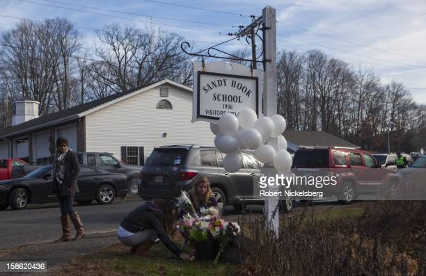 Local residents place flowers near the Sandy Hook Elementary School December 15 2012 in Sandy Hook Connecticut for the 28 children and faculty shot...