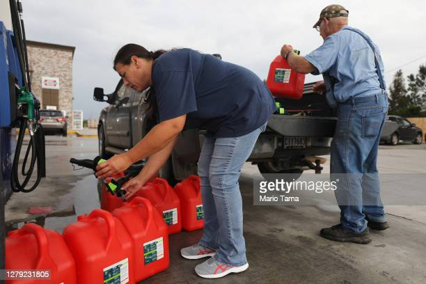 Local residents place unfilled gas cans back in their truck after discovering there was no regular gasoline left at the station as they prepare for...