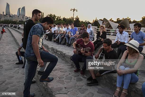 Local residents play guitars by the sea at Baku's Boulevard ahead of Baku 2015 the first European Games on June 11 2015 in Baku Azerbaijan