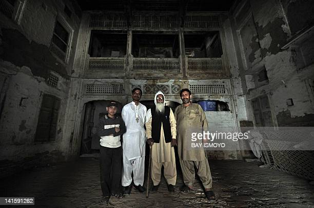 Local residents pose inside a 200year old house undergoing ownership disputes between heirs residents and the local government in the old town...