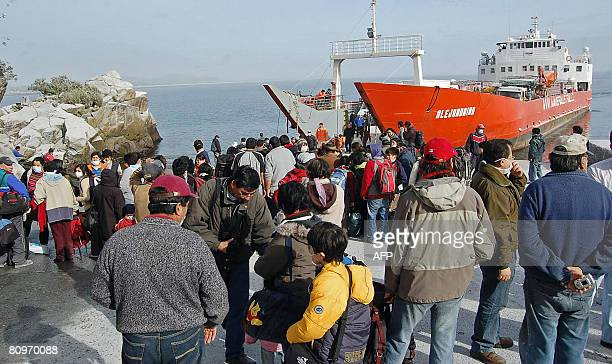 Local residents prepare to board a ship during evacuation operations following the eruption of the Chaiten volcano in the locality of Chaiten some...