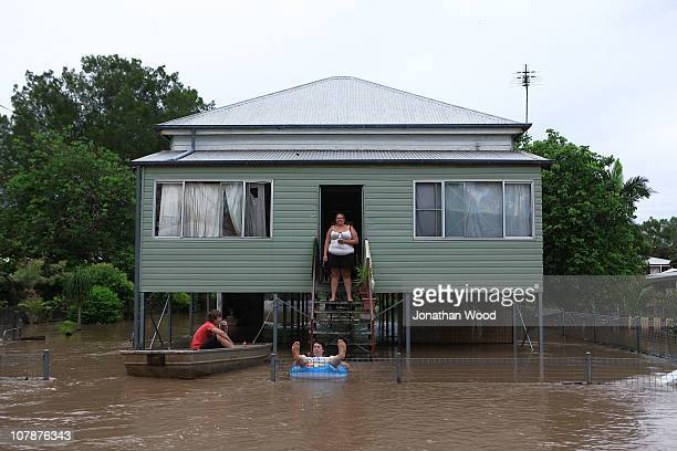 Local residents relax as their home is surrounded by flood waters on January 5 2011 in Rockhampton Australia All eyes are on the central Queensland...