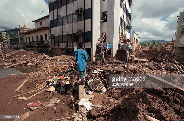 Local residents remove the mud from the streets of Tegucigalpa the Hondurian capital 13 November 1998 after the passage of hurricane Mitch Local...