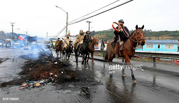 Local residents riding horses pass along a burnt out barricade in a street of Castro Chiloe island about 1230 km south of Santiago on May 9 2016...