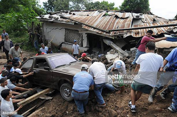 Local residents salvage a car on October 24 2008 from a wrecked sector at El Eden neighborhood on the side of El Picacho hill in Tegucigalpa Some...