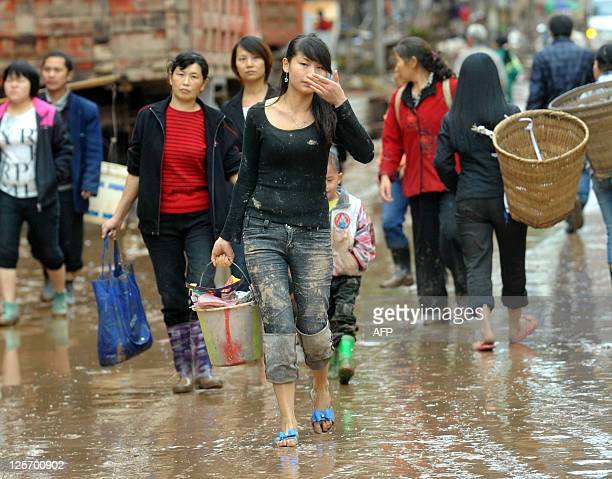 Local residents salvage their belongings after flood waters swarmed the city of Guangan southwest China's Sichuan province on September 19 as...