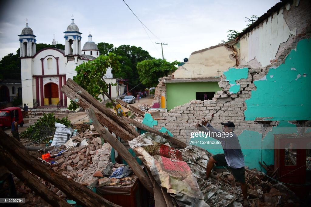 TOPSHOT - Local residents search for belongings amid the ruins of their home, knocked down by Thursday night's 8.2-magnitude quake, in Juchitan, Oaxaca, Mexico, on September 10, 2017. Rescuers pulled bodies from the rubble and grieving families carried coffins through the streets Saturday after Mexico's biggest earthquake in a century killed 65 people. /
