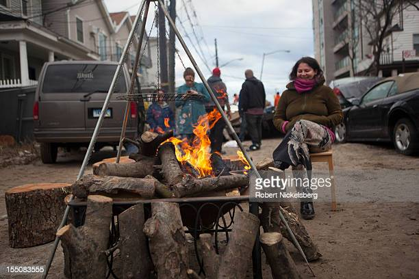 Local residents sit around a wood fire in Rockaway Beach after Superstorm Sandy swept through on October 31, 2012 in the Queens borough of New York...