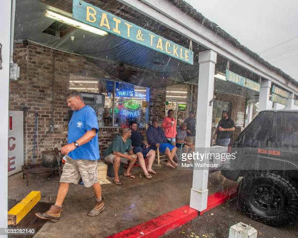 Local residents sit outside the Pawleys Island Supplies drinking beer as customers come and go at the only open store for miles around on September...