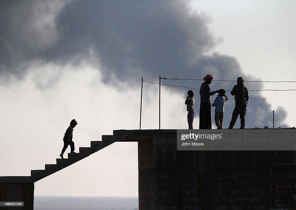 Local residents speak with a Kurdish soldier while an oil well burns in the distance on November 10, 2015 near the ISIL-held town of Hole in the autonomous region of Rojava, Syria. Troops from the Syrian Democratic Forces, a coalition of Kurdish and Arab units, are attacking ISIL extremists in the area near the Iraqi border. The predominantly Kurdish region of Rojava in northern Syria has become a bulwark against the Islamic State. Their armed forces, with the aid of U.S. airstrikes and weapons, have been battling ISIL, who had earlier captured much of the region from the Syrian regime.