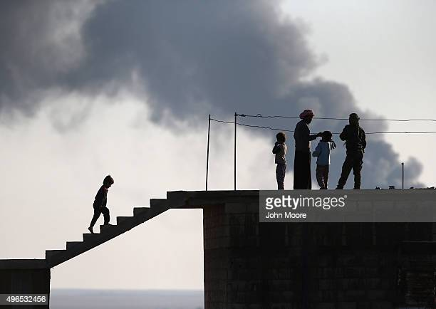 Local residents speak with a Kurdish soldier while an oil well burns in the distance on November 10 2015 near the ISILheld town of Hole in the...