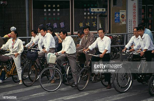 Local residents spotted riding through town on their bicycles an efficient form of transport given the amount of traffic conjestion in Shanghai China...