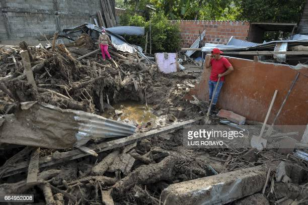 Local residents stand amid the ruins of a house destroyed by mudslides caused by heavy rains in Mocoa Putumayo department southern Colombia on April...