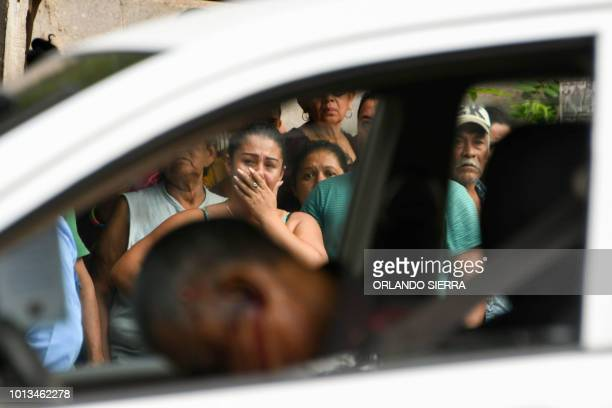Local residents stand at the crime scene where a taxi driver was shot dead by alleged gang members for refusing to pay them a war tax in Tegucigalpa...