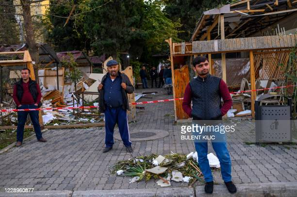 Local residents stand in a street after it was hit by a missile in Gandja, Azerbaijan, on October 8 near the disputed Nagorno-Karabakh province's...