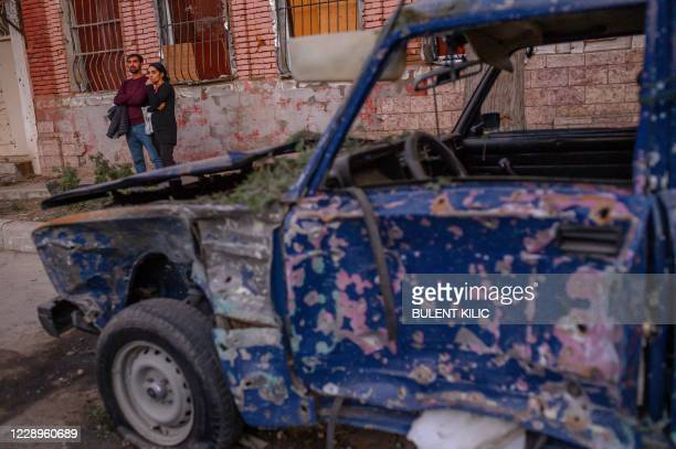 Local residents stand in a street near a damaged car after it was hit by a missile in Gandja, Azerbaijan, on October 8 near the disputed...