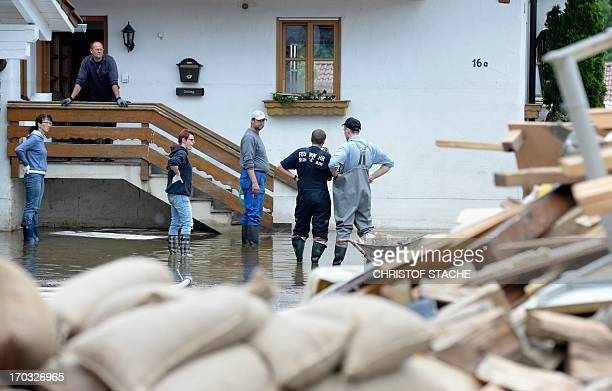 Local residents stand in front of a house that was hit by the floods of the river Danube in Fischerdorf near Deggendorf southern Germany on June 11...