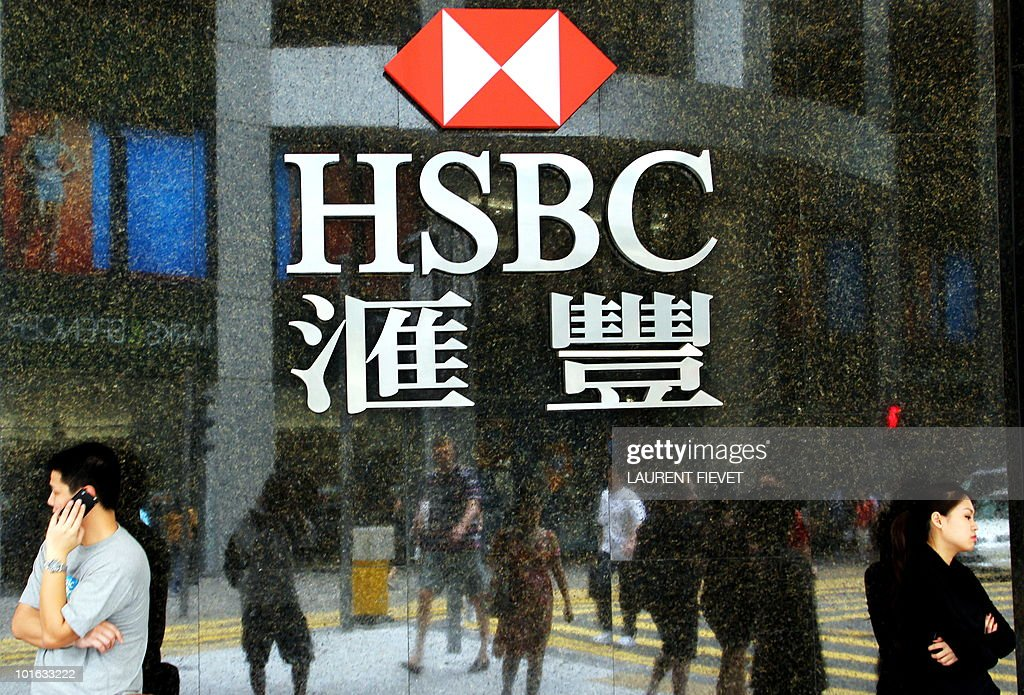 Local residents stand in front of the Hong Kong and Shanghai Banking Corporation (HSBC) logo in Hong Kong on June 5, 2010. HSBC has become the latest bank to respond to regulatory pressure to spin off its private equity activities by starting talks about management buy-outs at five of its private equity businesses overseeing 8.8 billion USD of assets.