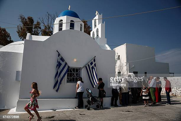 Local residents stand outside a Greek orthodox church to listen to a religious ceremony in the town of Fira on the island of Santorini Greece on...