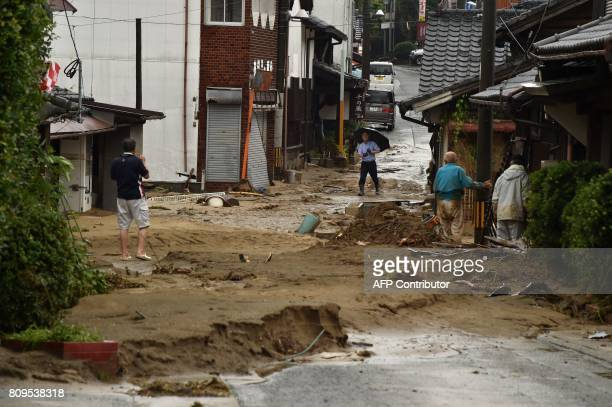 Local residents stand outside their homes on a street filled with mud and silt following heavy flooding in Asakura Fukuoka prefecture on July 6 2017...
