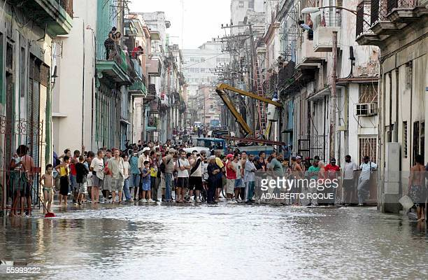 Local residents stay aside a flooded street 24 October 2005 after the devastating passage of Hurricane Wilma Havana residents woke up to inundated...