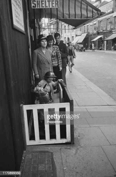 Local residents take a last look at approaching planes before entering an underground air raid shelter on a street in Dover England during the Battle...