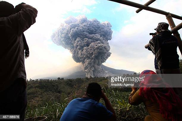 Local residents take photos of the eruption of Mount Sinabung volcano ash cloud issued a gigantic long as seen from the Three Pancur village Karo...
