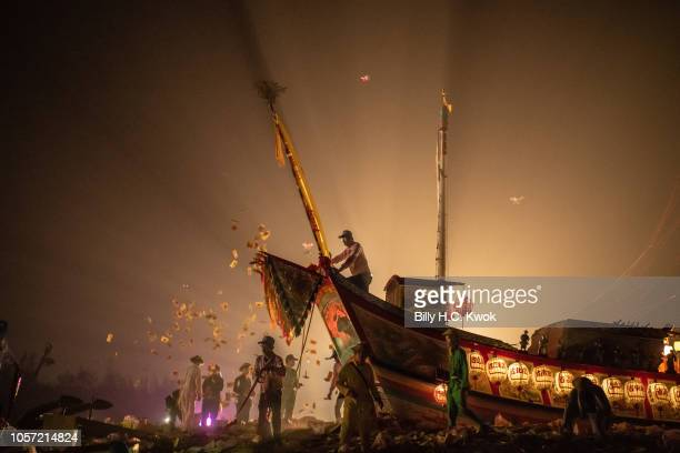 Local residents throw the ghost money in front of the 'Wang Yeh's Boat' a 13meter finely crafted ancient warship made of paper and wood for burning...