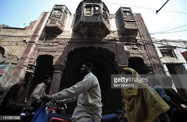 Local residents travel past a dilapidated building in the old town section of Multan on March 17 2012 Multan one of the oldest cities in the Asian...
