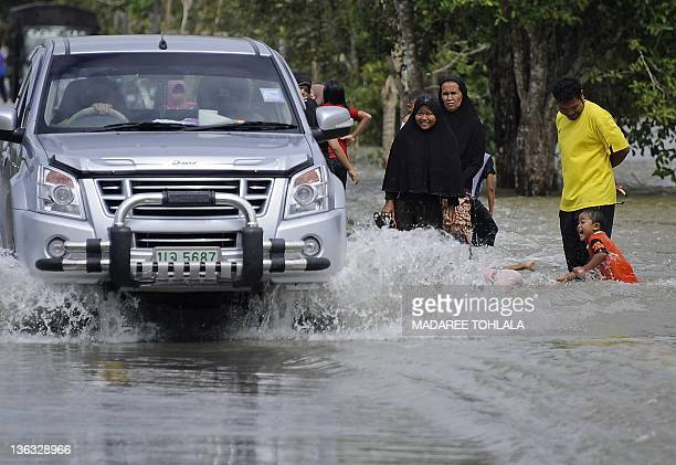Local residents travel through floodwaters after flash floods hit Thailand's southern Narathiwat province on January 2 2012 Heavy rain and flash...