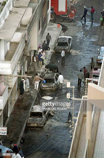 Local residents view burnout wrecks of cars in central Dakar on February 16 1994 after they were set light by hundreds of youths during a violent...