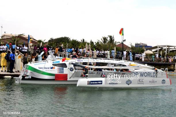 Local residents wait for the Row4ocean rowing trimaran to leave Dakar to cross the Atlantic on December 14 2018 A rowing trimaran took off on...