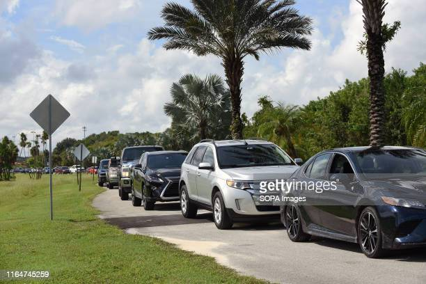 Local residents wait in their vehicles to receive a limit of ten sandbags per car at a sandbag distribution location in preparation for the arrival...