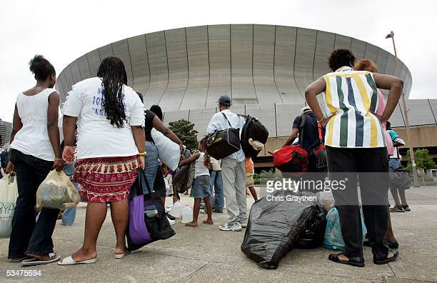 Local residents wait with their belongings for the New Orleans Superdome to open as an emergency shelter ahead of Hurricane Katrina August 28 2005 in...
