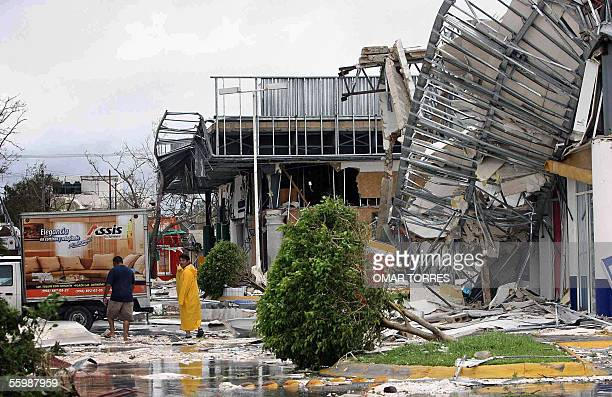 Local residents walk 23 October 2005 along a collapsed metal structure destroyed by the sheer force of Hurricane Wilma in Cancun Mexico Although...