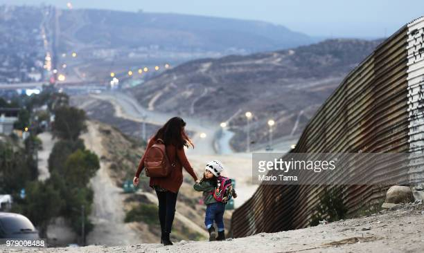 Local residents walk along the Mexico side of the USMexico border on June 19 2018 in Tijuana Mexico US President Trump's Mexican border policy has...