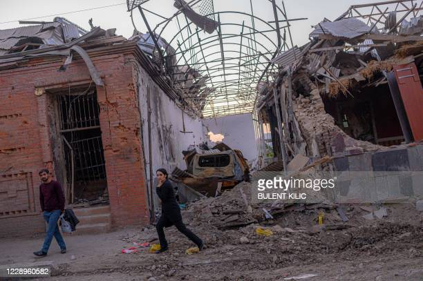 Local residents walk in a street after it was hit by a missile in Gandja, Azerbaijan, on October 8 near the disputed Nagorno-Karabakh province's...