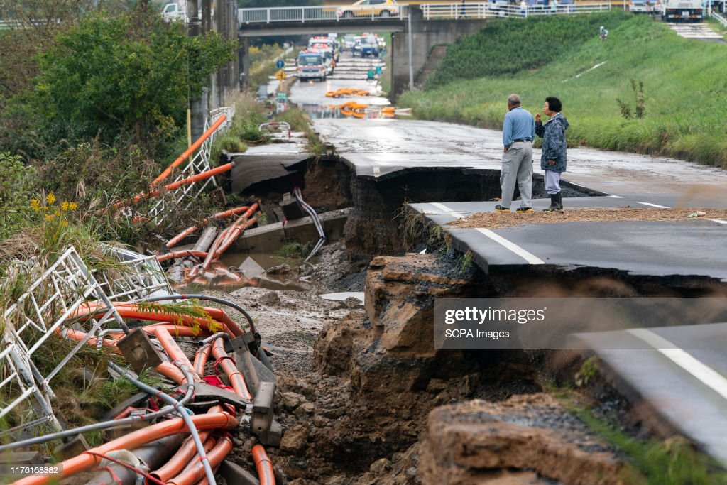 Local residents walk on a collapsed road following the... : News Photo