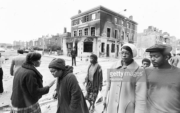 Local residents walk past a burnt out pub in Brixton after a second night of rioting in the area 13th April 1981