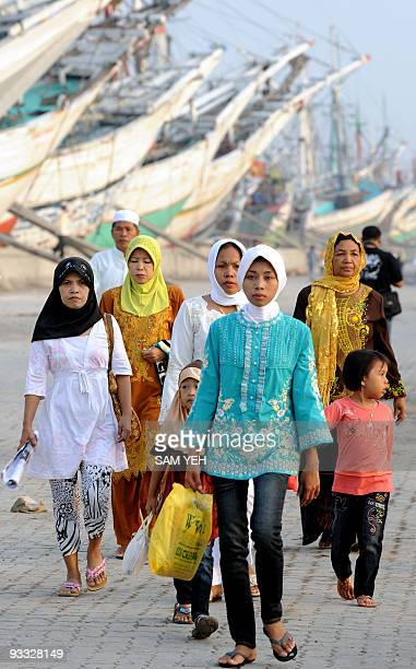 Local residents walk past a group of fishing boats at the Sunda Kelapa port in Jakarta on October 1 2008 Muslims around the world are celebrating the...