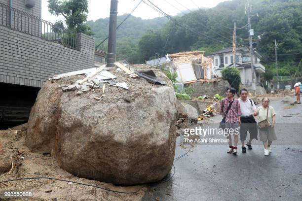 Local residents walk past a hug rock flown by a landslide due to heavy rain on July 7 2018 in Hiroshima Japan 51 people were killed and 58 missing...