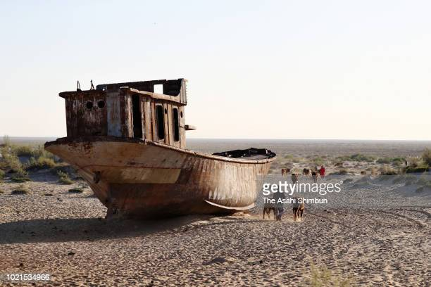 Local residents walk past a wrecked fishboat as water of the Aral Sea had been receded at socalled 'Ship Graveyard' on May 2 2018 in Muynak...
