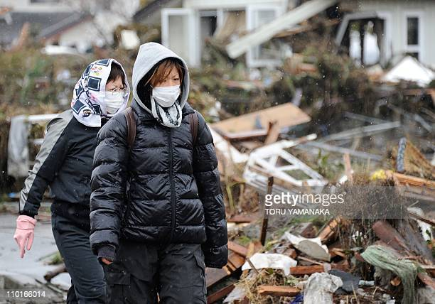 Local residents walk past collapsed houses and debris left by the March 11 tsunami and earthquake in Natori in Miyagi Prefecture on March 16 2011...